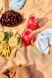 Picnic at the park on the grass: tablecloth, basket, healthy food and accessories. Stock Photos