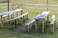 Picnic place for rest on green grass. Lit by bright summer sun old weathered wooden tables and benches on primitive fence made fro. M beams background. Tourism royalty free stock image