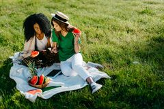 Picnic portrait of two multi-race girl friends. They are laughing while watching something funny on the mobile phone and. Eating the watermelon royalty free stock image