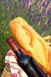 A picnic in Provence. Red wine and baguette in a picnic basket amongst the lavender Stock Images