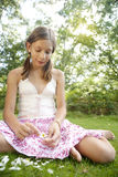 Picnic Pulling Petals. Teenage girl pulling petals off a daisy flower, while sitting down on green grass, in a sunny forest Stock Photo
