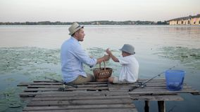 Picnic by river, dad and son after fishing sitting on pier near water among reeds enjoy socializing and eat on vacation. Picnic by river, dad and son after stock video