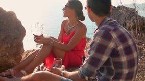 Picnic romantico delle coppie amorose con il Mountain View e della spiaggia al tramonto video d archivio