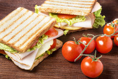Picnic sandwiches. Sandwiches with chicken breast, salad, cheese and tomatoes on wooden table Royalty Free Stock Images