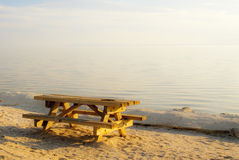Picnic by the Sea. Empty seaside picnic benches invite a quiet moment before sunset Stock Photos