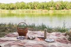 Picnic set, metal Cutlery, thermos, plates tea cups. brown plaid and napkin from the lake in the background. green grass. Sunny su Stock Image