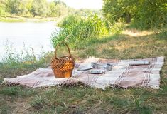 Picnic set, metal Cutlery, thermos, plates tea cups. brown plaid and napkin from the lake in the background. green grass. Sunny su Royalty Free Stock Photo