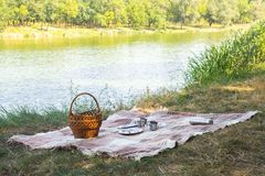 Picnic set, metal Cutlery, thermos, plates tea cups. brown plaid and napkin from the lake in the background. green grass. Sunny su Stock Photos