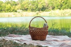 Picnic set, metal Cutlery, thermos, plates tea cups. brown plaid and napkin from the lake in the background. green grass. Sunny su Stock Images
