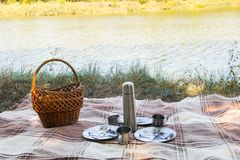 Picnic set, metal Cutlery, thermos, plates tea cups. brown plaid and napkin from the lake in the background. green grass. Sunny su Stock Photo