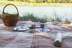 Picnic set, three persons. metal Cutlery, thermos, plates, tea cups. brown plaid and napkin from the lake in the background. green Royalty Free Stock Photography
