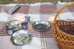 Picnic set, three persons. metal Cutlery, thermos, plates, tea cups. brown plaid and napkin from the lake in the background. green Royalty Free Stock Photo