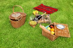 Picnic setting. With Champagne wine, grape, glasses, grape and picnic hamper, picnic basket and blanket Royalty Free Stock Photo