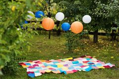 Picnic setting outdoors with plaid and paper lanterns. Celebration, party concept, romance, love date theme. Picnic setting outdoors with plaid and paper stock photo