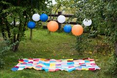 Picnic setting outdoors with plaid and paper lanterns. Celebration, party concept, romance, love date theme. Picnic setting outdoors with plaid and paper royalty free stock images