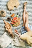 Picnic setting with woman in dress, wine, fruits and baguette Royalty Free Stock Photos