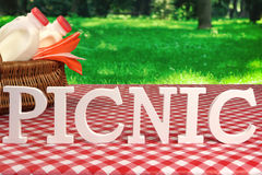 Picnic Sign On Table With Basket And Red Tablecloth Royalty Free Stock Photos
