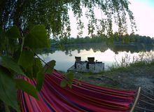 Picnic site. lake, picnic, nature, outdoor. Rest on the lake, a hammock and chairs on the stage stock photos