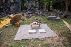 Picnic su erba in rovina antica Picnic di stile giapponese con gli ombrelli e la piccola tavola immagine stock libera da diritti