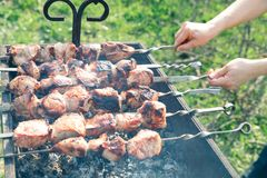 Picnic in the summer. Preparation of a shish kebab on opened the uyena and coals outdoors. Two hands overturn skewers with meat Royalty Free Stock Photo
