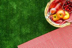 Picnic in summer with products, apples, cherry, drinks on green grass texture background top view space for text. Basket with food. Picnic in summer with stock photos