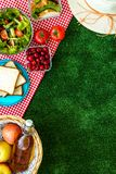 Picnic in summer with products, sandwich, salad, fruits, drink and hat on green grass texture background top view mockup. Basket with food. Picnic in summer with stock photo
