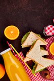 Picnic. Summer Time Rest. Picnic on brown table. Red checked tablecloth, basket, healthy food sandwich and fruit, orange juice.  Summer Time Rest. Flat lay Stock Photo