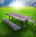 Picnic table. A old wooden picnic table in a grassy field Royalty Free Stock Image