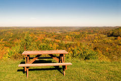 Picnic table in autumn scene. Picnic table overlooking colorful forest in autumn scene Royalty Free Stock Photography