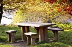Picnic table, autumnal colours of trees at Peak District,  Doves. Tone Reservoir, England, UK Royalty Free Stock Image