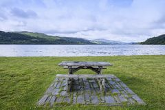 Empty picnic table with Snowdonia in distance North Wales UK. Picnic table with Bala Lake or Llyn Tegid with Aran Fawddwy mountains in Wales UK Royalty Free Stock Photos