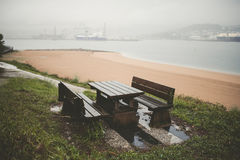 Picnic table and benches in a park on a rainy day Royalty Free Stock Photos