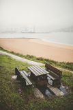 Picnic table and benches in a park on a rainy day Stock Photos