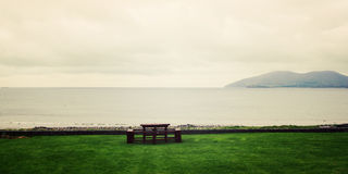 Picnic Table Benches and seascape in Waterville, County Kerry - vintage effect. Royalty Free Stock Photography