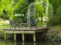 Picnic table and chairs located on a quiet river Stock Images