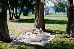 Picnic table with decor and colored ribbons on grass near trees Stock Photos