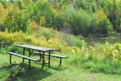 Picnic table by forest and lake. Stock Photo