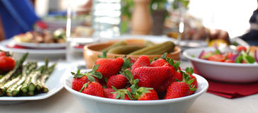 Picnic table with grilled foods and strawberries Royalty Free Stock Photo
