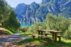 Picnic table by the lake. Open air picnic table on the beautiful summer day by the Lago di Garda, Lake Garda, Trento, Italy Royalty Free Stock Photography