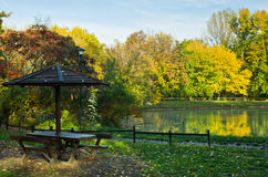 Picnic table by the lake surrounded by the forest in autumn colors Stock Photography