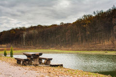 Picnic table near lake in autumn forest Stock Photo