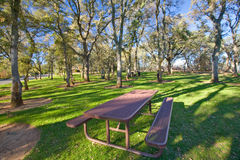 Picnic table in public park. Picnic table in a lush green public park with oak trees Royalty Free Stock Images