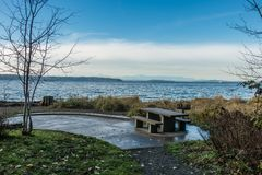 Picnic Table and Puget Sound. A picnic table sits on shore at Seahurst Park in Burien, Washington. The Olympic Moountains can be seen across the Puget Sound stock photos