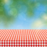 Picnic table with red checkered pattern of linen tablecloth and blurred nature background vector illustration. Checkered tablecloth textile for garden table Royalty Free Stock Images