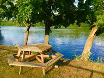 Picnic Table By A River. A picnic table by a river Stock Photo