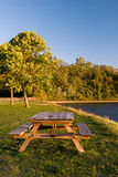 Picnic table by scenic lake. Scenic view of wooden picnic table by side of lake, forest in background Royalty Free Stock Images