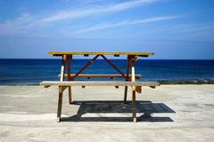 PICNIC TABLE & SEA. Scenic view of wooden picnic table on white sandy beach with sea and blue sky background Royalty Free Stock Image