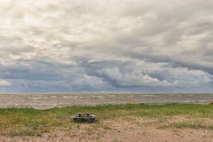 Picnic table by the sea. Round table for a picnic on the shore of the Baltic Sea against the background of beautiful clouds near the horizon Royalty Free Stock Photography