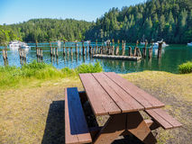 Picnic table at the shore of the bay  with moored boats Stock Image