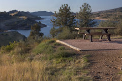 Picnic table on shore of mountain reservoir royalty free stock photo